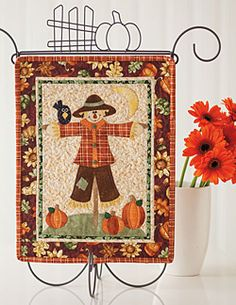 Pick of the Patch, featured in Love of Quilting September/October 2013, is a mini quilt pattern featuring an appliqué scarecrow and pumpkins. Quilt by Kelly Mueller.