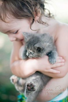 A CHILD HUGGING A KITTEN.