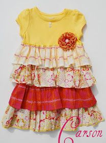 RUFFLED DRESS: Dress is made from attaching 4 layers of ruffles to a yellow t-shirt and has a ruffled flower accent with a covered button. sew on some flowered buttons under the neckline. Use yellow designer 6 thread to serge the edges of the bottom ruffle and top ruffle as well as the flower.