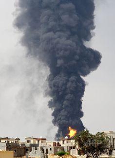 ロケット弾の直撃を受けて火災が発生したリビア・トリポリ(Tripoli)郊外の燃料貯蔵施設から上る黒煙(2014年7月28日撮影)。(c)AFP/MAHMUD TURKIA ▼30Jul2014AFP|大火災続き戦闘機墜落や議員誘拐も、リビア 治安悪化の一途 http://www.afpbb.com/articles/-/3021788