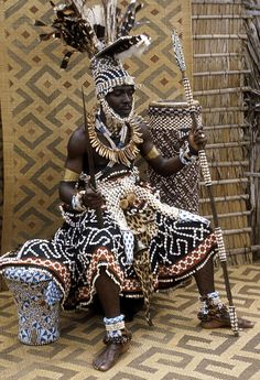Nyimi Kot a-Mbweeky III is wearing the same attire depicted in Ndop statues. If you look closely you can see the board extension on top of his head. Most of Kuba art is made up raffia fibers ceramic glass beads and cowries. This photograph was taken by Elisofon in early 1970