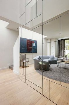 A geometric mirrored wall conceals closets and storage spaces, which are located behind the touch latch mirrored doors.