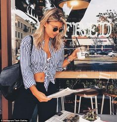 Trim: Natasha Oakley showed off her washboard abs in a white and blue striped crop-top shi...