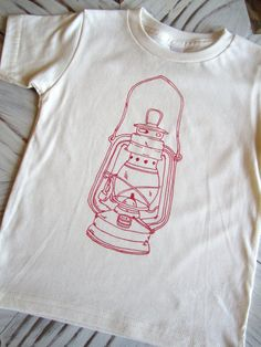 We love the unique look of hand printed textiles and their ability to capture the style and feel of honest hand made goods. This 100% organic cotton American Apparel brand toddler shirt has been screen printed with our original hand drawn vintage lantern print. This lantern is the perfect outdoorsy and whimsical illustration for a little boy or girl. We only use the highest quality fabric inks that are sure to stand up to the everyday hustle and bustle of your little one.  Available Sizes: 2…