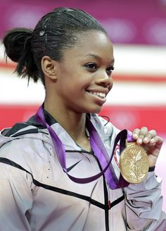 Gabby Douglas displays her gold medal during the artistic gymnastics women's individual all-around competition.