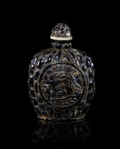 A Tortoise Shell Snuff Bottle,  centered with a circular reserve depicting a bird beneath a pine tree, against a bamboo segment modeled ground.
