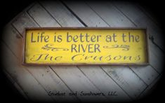 "Rustic Wooden Sign With Frame, Custom Family Name Sign, Life Is Better At The River, Over The Door Sign, Handmade Wooden Sign,Gifts Under 50      This beautiful, framed rustic family name sign is the perfect addition to your riverfront property. (Makes a great housewarming gift too) This sign is handcrafted, stained and hand painted. It is heavily distressed to give a very rustic look and features the words,""Life is better at the river."" No two are exactly alike. It comes with 2 saw tooth…"