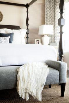 A gray upholstered bench placed at the foot of this canopy bed makes a comfortable, stylish relaxing spot.