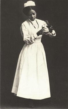 """A reproduction of a nurse's portrait from the 1920s entitled """"A Taste of Her Own Medicine,"""" a comedic portrayal of the nurse in search of romance as she mixes a love potion, 1987. Pictures of Nursing: The Zwerdling Postcard Collection. National Library of Medicine"""