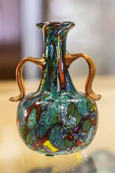 """Beautiful Murano vase with applied handles. Melted canes in end-of-day style with yellow glass handles. Old Murano sticker on base. Measures 5.75"""" tall."""