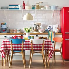 seriously eye catching retro modern kitchen - love the red fridge and oversized gingham table cloth... the other colours present such as orange, yellow, white and blue combined with wood and white kitchen mean the red does not take over at all