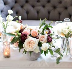Low concrete vase spilling with bay laurel, dusty miller, silver dollar eucalyptus, plumosa, burgundy scabiosa, ivory spray roses, light pink astrantia, blush quicksand roses, and white dendrobium orchids surrounded at the base by white modern votives