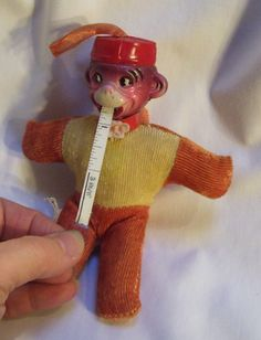 "Circa 1943 celluloid head and plush body figural monkey tape measure pin cushion. The monkey measures 6"" tall, 5 1/4"" from tip of outstretched arm to tip of outstretched arm. The label to the side reads ""Japan"". The monkey has a pink glower sewn to his red plastic collar. The original cardboard hand tag is not attached but it did come with the piece. It reads ""Pull my tongue for a tape measure, use my body for a pin cushion. The patent number is for the year 1943."