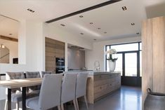 In een zeer strak interieur is deze moderne keuken een opvallend element dat met ruw eikenhout de woning karakter geeft.
