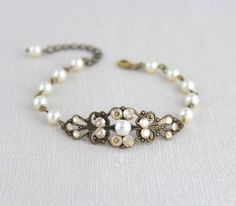 This beautiful bracelet is created with a highly detailed antique brass filigree which I dressed with Swarovski ivory pearls and Swarovski Golden shadow crystal rhinestones. Simple but detailed. Bracelet measures 6 inches and extends to 8 inches. This is an original design by ©