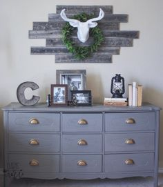 I love the rustic wall piece and the frames on the gray dresser. It is a balance of crisp and clean with rustic charm :)