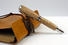 *NOTE - the book is a photography prop and not included.    LASER ENGRAVING IS AVAILABLE ON REQUEST - cost around £40 extra, the engraving is done behind the finish which is built up over it to ensure a long lasting, smooth and flawless finish.     This pen is a hand turned, hand made oak fountain Pen of the highest quality.    You can specify this pen as a roller-ball, or fountain pen in various wood finishes.     Copy and paste the link below into a new window to see high-definition photos…
