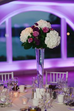 White hydrangea and lavender rose arrangements on top of tall pilsner vases at Candlewood Inn Brookfield, CT