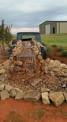 Rustic, western yard decor. Old pickup waterfall. Large mountain rocks and gravel.