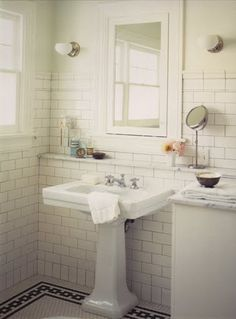Bathroom by Kevin Oreck with pedestal sink, white subway tile wall and a porcelain mosaic tile floor with black chain link border