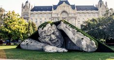 """Artist Ervin Loránth Hervé created an impressive sculpture """"Popped Up,"""" depicting a giant man, crawling out of the subterranean world. The polystyrene sculpture took place at Széchenyi Square in Budapest, Hungary, and was one of the highlights for the international contemporary art fair Art Market Budapest 2014."""