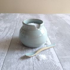 Little pop bellied pot; salt pig or sugar bowl. It comes with an adorable hand made spoon. A thoughtful gift for any foodie. This cute little pot is thrown on my wheel using stoneware clay. I shape the foot and leave it to dry before cutting the groove for the hand made spoon. The pot is dried out completely before firing and decorating with a beautiful duck egg glaze which lets the natural speckle of the clay show through. The pot & spoon are fired for a second time to 1250 degrees cent...