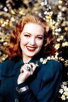 Actress Linda Darnell in a blue suit with auburn hair, 1940s.