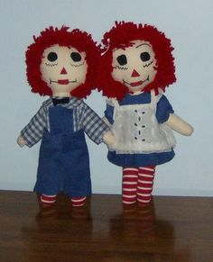 "Two 14"" dolls. Skin tone cotton, stuffed with 100 % polyester Eversoft. Faces embroidered by machine. Hair 100% polyester wool. Clothing: Blue corduroy, blue gingham, white eyelet. Red and white strip"