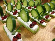 Healthy snack for preschool garden-themed party. Celery, cream cheese, cucumber, chives, pomegranate seeds and reduced balsamic vinegar. Trimming a strip from the bottom of the celery stick helps it to sit flat.