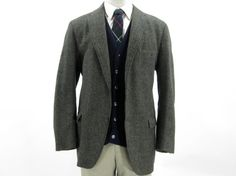 Vintage Harris Tweed herringbone sport coat in shades of green, brown, yellow and black. One breast pocket, two flapped hip pockets, and three button front.    Inner lining is heavily torn and in poor condition, however it is not visible from the outside and does not effect the utility of the coat. No size is listed, but measurements indicate a size 44, or men's large. $78.00