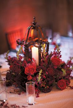 Tall and low arrangements of roses, berries, and dahlias surrounding wrought-iron lanterns and candelabras. Rhee Bevere Photography.