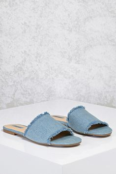 A pair of denim slide sandals featuring a frayed trim, an open toe, and a low heel.