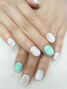 white and mint green with gold crosses nail art design