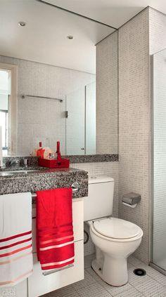 """O espelho do banheiro ocupa quase toda a parede, tocando o teto: uma maneira de criar a impressão de que o espaço é maior. """"Também dá um toque de requinte"""", revela a arquiteta Andrea Del Monaco. Uma bandeja colorida sobre a bancada (Boutique de Achados, R$ 69,90) deixa cosméticos e perfumes à mão de forma graciosa e organizada. Toalhas: de rosto, modelo Lumina, da Karsten (50 x 80 cm). Zelo, R$ 15,90 cada."""