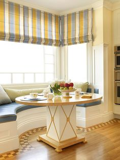 This beautiful built in curved banquette has a plethora of character within its small space. Large, bright windows with multicolored striped roman shades add charm to this well designed nook.   Caption by Jenn Brown