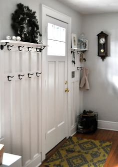 board and batten entryway.  Thats a good amount of hooks too.  Just needs a storage bench of some kind