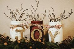 """Easy DIY Mason Jar Christmas Decor. """"JOY"""".  • Mason Jars • Chalk Paint for Jars • Acrylic for letters • Ribbon • Fake forestry pieces • Wood Letters • Sand paper  》Paint jars with chalk paint. After they are dry, use sand paper to distress them, particularly over the lettering. Then, tie ribbon around the top and place forestry inside. When done with those, paint letters the color of your choice and hot glue them on to the jars. Super easy!"""