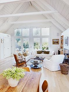 white living room with a high peaked ceiling  I love the double French doors; they let in soooo much light!