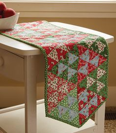 "Make this cute red and green holiday table runner quilt pattern come to life with 2½"" pre-cut fabric strips! Makes a wonderful gift for this holiday season!"