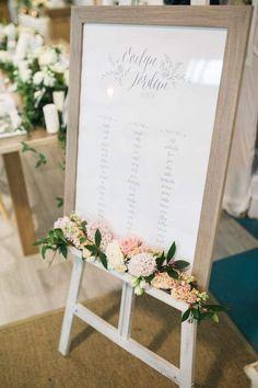 Sitzplan in einfachem Bilderrahmen mit schönem Blumenschmuck auf Staffelei