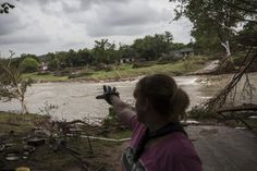Amy Gilmour describes how the Blanco River crested at a record 43 feet during the Memorial Day weekend floods while helping pick up debris from the backyards of flood damaged homes in Wimberley, Texas May 26, 2015. REUTERS/Tamir Kalifa