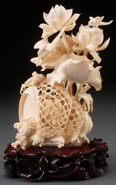 """A VERY FINELY CARVED CHINESE IVORY FIGURAL GROUP, 20TH CENTURY. In the form of a large seashell internally decorated with a carved village scene surmounted with crabs atop stylized waves with large extending lotus blossoms on thorny stems, terminating with an egret, king fisher, and dragonfly. The base inscribed in pencil """"China Exhibit 1984 World's Fair, New Orleans, LA"""", and raised on a conforming pierced hardwood stand."""