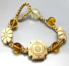 This is a very simple macrame bracelet hand knotted with a shiny synthetic gold colored cord. the beads are cream colored resin and 8mm honey/amber glass. The knots used are lark's head and the square knot. It is finished with a loop and bead closure. The closure bead is acrylic.  Very easy to make!