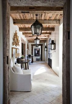 Rustic villa entry hall with exposed wood beams and hanging iron lanterns down the hallway.