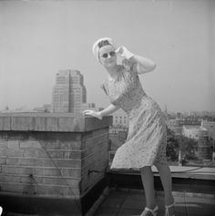 A model poses for the camera on a Bloomsbury rooftop as she shows off a cyclamen and white printed silk dress, the skirt blown by the breeze, worn with a white turban and white gloves ~