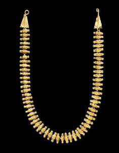 A ROMAN GOLD NECKLACE   CIRCA 3RD CENTURY A.D.   Composed of a length of figure-8 loop-in-loop chain, each link backing a hollow sheet ornament in the form of two joined triangles, a groove in between, balls on the ends, the hook-and-loop closure each ornamented with a sheet triangle