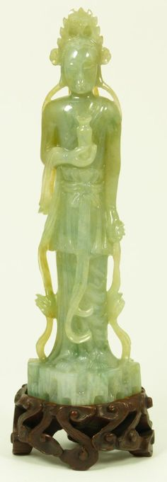 "CHINESE CARVED JADEITE FIGURE OF GUANYIN Chinese hand carved jadeite figure depicting a standing Guan Yin. Mottled white and green jade colors. Includes fitted reticulated cloud form wooden base. Measures 8 5/8"" height (21.9cm). Jadeite weight of 436 grams. Provenance: Christie's East March 24, 1998 sale, lot 53."