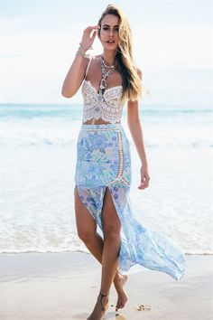 The flattering Emilia Maxi Skirt is made from blue and green floral fabric and features sheer lace panels throughout. The skirt is a fitted mermaid style that flares slightly from the waist down with two front splits. By Sabo Skirt.
