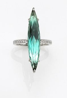 A tourmaline and diamond ring, Nardi  centering an elongated marquise-cut greenish blue tourmaline, weighing 6.92 carats, measuring approximately 33.50 x 6.40 x 5.30mm., completed by round brilliant-cut diamond shoulders; unsigned, attributed to Nardi; mounted in platinum.