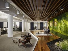 A wall filled with plants and flooring that looks like an outdoor patio creates a tranquil mood in the office.